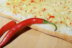 Garlic bread and red chili peppers Royalty Free Stock Photography