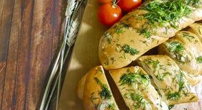 Garlic bread ruddy on a wooden board, cherry. Garlic bread ruddy on a wooden board cherry tomato wheat earn Royalty Free Stock Photo