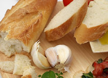 Garlic with bread and tomatoes. Mediterranean ingredients including bread, olive oil and tomato Royalty Free Stock Photos