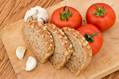 Garlic bread and tomatoes. Garlic bread slices and tomatoes on wood board Stock Image