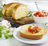 Garlic bread  topped with tomato, garlic and herbs Stock Images