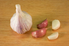 Garlic on Breadboard - 5. Garlic cloves on a brown breadboard Stock Image