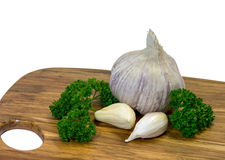Garlic. Bulb and cloves of garlic on wooden chopping board with parsley Stock Image