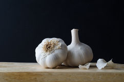 Garlic Bulb Heads on Chopping Board. Still life arrangement of two whole, unpeeled garlic bulb heads, with some loose papery skin scattered on wooden chopping Royalty Free Stock Photo