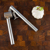 Garlic bulb and press on wooden surface Royalty Free Stock Photography