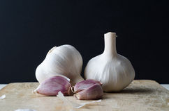 Garlic Bulbs and Cloves on Chopping Board Stock Photography