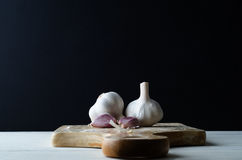 Garlic Bulbs and Cloves on Wooden Chopping Board against Black Stock Photos