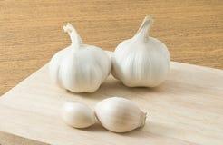 Garlic Bulbs and Garlic Cloves on Cutting Board Stock Photo