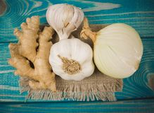 Garlic bulbs, ginger and onion on blue wooden table. Natural medicine. Close up on garlic bulbs, ginger and onion on blue wooden table. Concept of natural Stock Photo