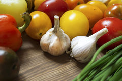 Garlic bulbs, green onion, pepper, tomatoes on wooden table Stock Photo