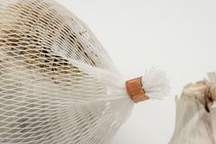 Close-up image of dried Garlic bulbs shown with the white, plastic netting in which they are sold in. The Garlic bulbs are to be used in food preparation. The Stock Photos