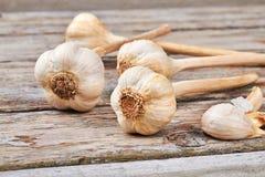Garlic bulbs on wooden surface. Royalty Free Stock Photos