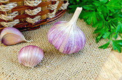 Garlic with burlap and a basket on the board Stock Photos