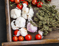 Garlic, cherry tomatoes and thyme herb on wooden board Stock Photos