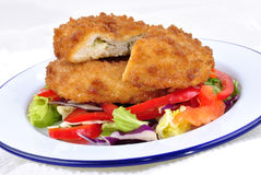 Garlic chicken kiev with mixed leaf salad Stock Photos