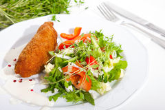 Garlic chicken kiev with mixed leaf salad Stock Photography