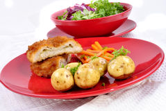 Garlic chicken kiev with young potatoes Royalty Free Stock Images