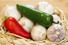 Garlic and Chilli Basket Close-up. Garlic and chillies in a rustic basket on a close up wooden surface Royalty Free Stock Photography