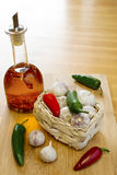 Garlic and Chilli Basket With Oil. Garlic and chillies in a rustic basket with a bottle of chilli oil on a wooden surface with copy space Stock Photos