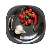 Garlic, chilli, tomato on a plate Royalty Free Stock Photography