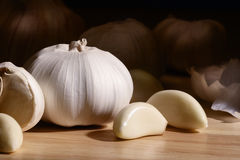 Garlic. Close up of garlic bulb and cloves on wooden surface Royalty Free Stock Images