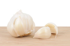 Garlic cloves. Whole, unpeeled garlic bulb on cutting board Stock Images