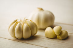 Garlic cloves and bulb on chopping board Stock Photo