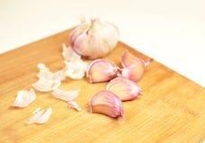 Garlic cloves on a cutting board. Garlic bulb and cloves on a yellow cutting board. Spices in the kitchen Stock Photos