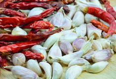 Garlic cloves  and dry chili peppers  on wood cutting board Royalty Free Stock Photo