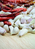 Garlic cloves  and dry chili peppers  on wood cutting board Royalty Free Stock Image