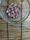 Garlic cloves in a glass bowl on the wood mat. Garlic cloves glass bowl wood stock image