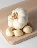 Garlic cloves and head. Three garlic cloves and a head on a wooden cutting board Royalty Free Stock Image