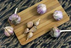 Garlic on a cutting Board. Garlic on a cloves and heads of garlic on a cutting Boardcutting Board Royalty Free Stock Image