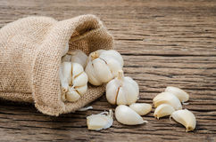 Garlic cloves in hemp sack bag on rustic wooden background. Thai herb and spices Stock Photography