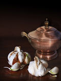 Garlic cloves and an old copper cask. Still life: old copper saucepan and garlic cloves, an essential and healthy spice in every kitchen stock image