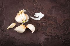 Garlic on Cutting Board. Garlic cloves on an old cutting board on a brown concrete background. Flat lay Royalty Free Stock Photo
