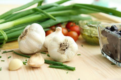 Garlic cloves, onion and tomatoes Stock Photography
