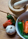Garlic cloves, peppers and mortat and pestle Stock Image