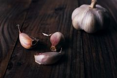 Garlic cloves on rustic wooden table. Vitamin healthy food spice image. Spicy cooking ingredient picture. Garlic cloves rustic wooden table. Vitamin healthy food stock image