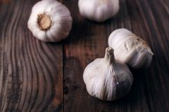 Garlic cloves on rustic wooden table. Vitamin healthy food spice image. Spicy cooking ingredient picture. Garlic cloves rustic wooden table. Vitamin healthy food stock photo