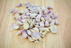 Garlic cloves on wood cutting board Stock Images