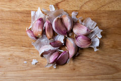 Garlic cloves on wooden chopping board Stock Image