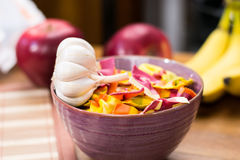 Garlic and colorful pasta in a cup with fruit in the background Stock Photography