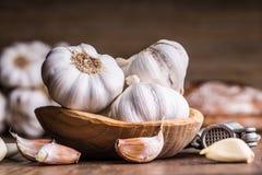 garlic Cravos-da-índia de alho e bulbo do alho na bacia de madeira do vintage Imagem de Stock Royalty Free