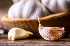 garlic Cravos-da-índia de alho e bulbo do alho na bacia de madeira do vintage Fotografia de Stock Royalty Free