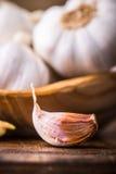 garlic Cravos-da-índia de alho e bulbo do alho na bacia de madeira do vintage Fotografia de Stock