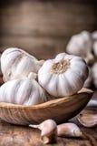 garlic Cravos-da-índia de alho e bulbo do alho na bacia de madeira do vintage Fotos de Stock Royalty Free
