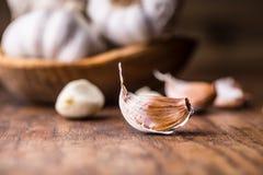 garlic Cravos-da-índia de alho e bulbo do alho na bacia de madeira do vintage Fotos de Stock