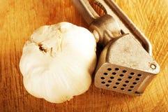 Garlic crusher and onion Stock Photo