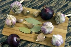 Garlic on a cutting Board. With the Bay leaf and pepper Royalty Free Stock Photo